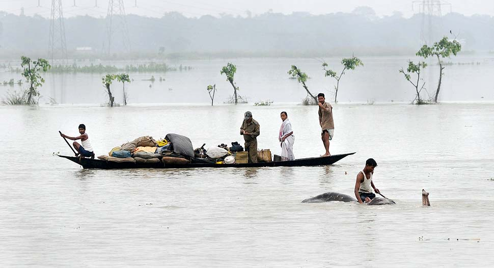A mahout moves an elephant to higher ground as villagers paddle with their belongings through flood waters in the Pobitora Wildlife Sanctuary, some 55 km from Guwahati, the capital city of Assam, India on June 28, 2012. Source: http://photoblog.nbcnews.com/_news/2012/06/29/12478381-india-floods-displace-more-than-850000?lite