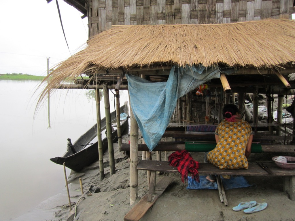 A woman weaving below a 'Chang ghar', a house made on an elevated platform. People from Mishing ethnic community live on chang ghars which is traditional way coping with floods. This photo taken in Matmora area of Dhakukhana subdivision also shows the backwaters of the river Brahmaputra. Photo – Parag Jyoti Saikia, SANDRP