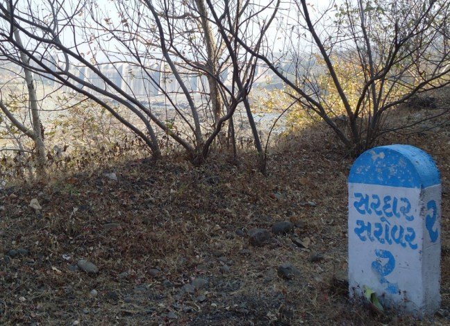 A milestone on the way to Sardar Sarovar, with the dam in the background. Photo: SANDRP