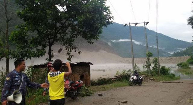 A man taking a photo of the artificial lake formed due to Sunkoshi River Blockade in Sindhupalchok