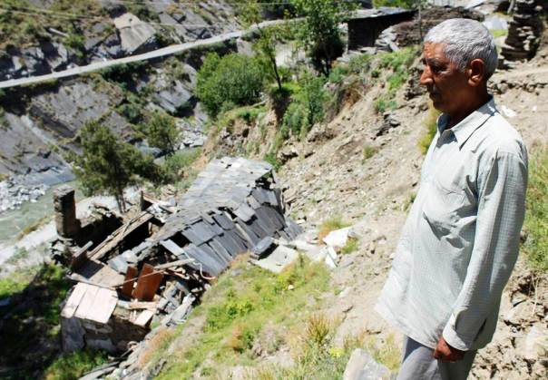 Shri Jagdish Sharma standing in front of the debris of his leftover house after the leakage tragedy
