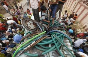 Slum dwellers collecting water from a water tanker (Source: India Water Portal)
