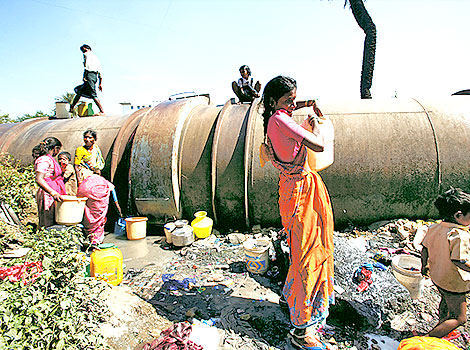 Slum dwellers collecting water from leaking pipes (Source: Hindustan Times)