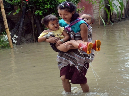 A woman carries her kids through a waterlogged road after heavy rains in Imphal on Saturday (17 July 2015). PTI Photo.
