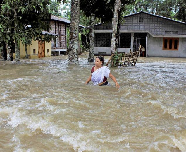 SWIRLING WATERS:A woman wades through flood water at a village in Sonitpur district of Assam on Wednesday. Nearly 65,000 people in over 155 villages across the State have been affected in the flood, following incessant rain.— PHOTO: PTI