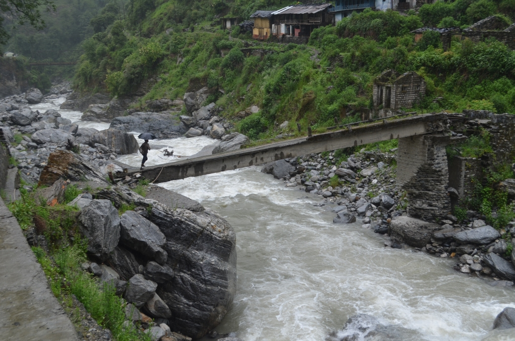 A villagers crossing the river over damaged bridge downstream of HGSHP