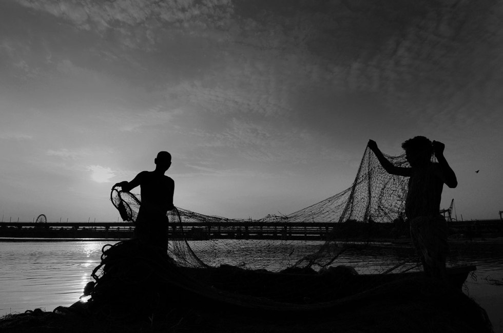 Noida, India - August 2016: The fishermen's day starts early, around five in the morning, when they go in for the first catch of the day. They emerge some four hours later, to cook their first meal of the day. Their river-based livelihood is reflected in what they eat - fish that they have caught themselves, cooked in different styles, and eaten twice a day. During the monsoons, they tend to construct makeshift tents on the banks of the swollen river, from where they launch their boats every morning, and where they spend their days and nights keeping a constant vigil on the river that gives them their livelihood. (Photo by Burhaan Kinu / Hindustan Times)