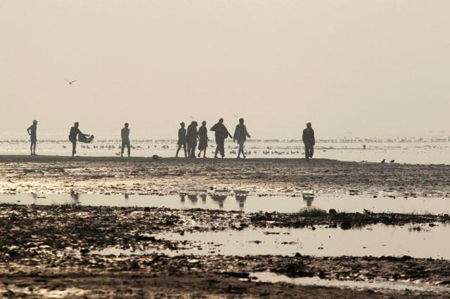 people-walk-along-the-bank-of-river-ganga-in-allahabad